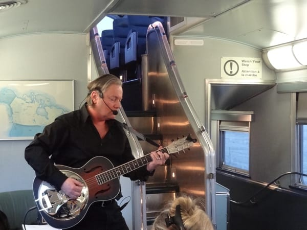 Poet-musician Paul Sanderson entertains poets and other passengers aboad The Canadian. VIA Rail's Artists on Board program features musicians on many trips. Photo copyright Laura Byrne Paquet.