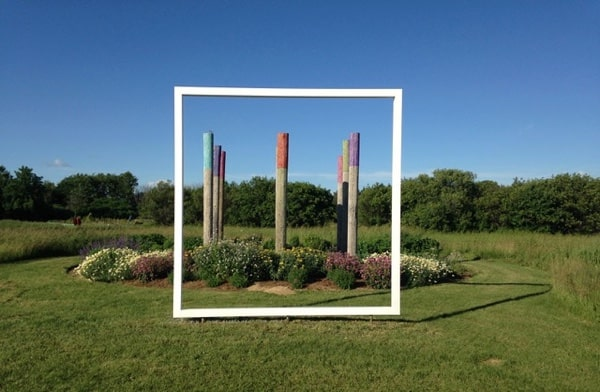 White frame surrounding sculpture in garden. Bee Haven by Engelina Schmitz with Canada Council Art Bank sculpture. Photo courtesy of Beyond the Edge: Artists' Gardens.