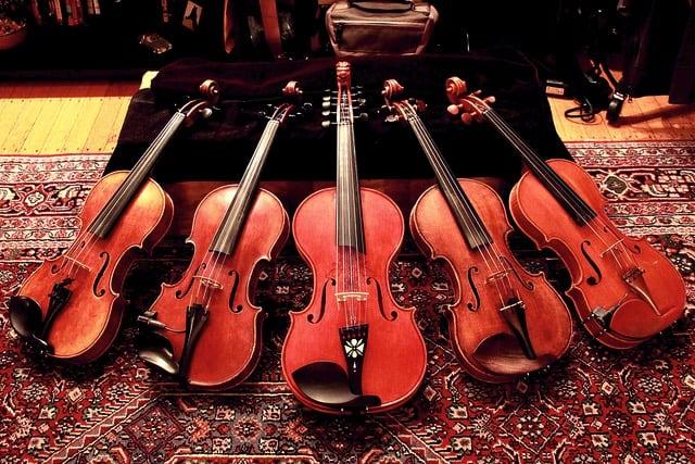 five fiddles (violins) on a carpet