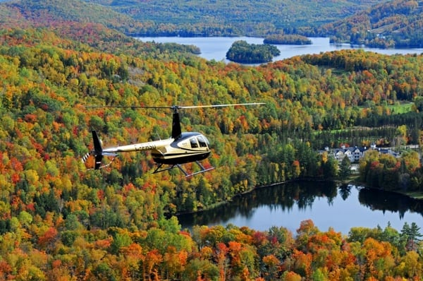 Helicopter flying over fall foliage and lakes in the Laurentians region of Quebec.