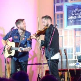 The Abrams playing guitar and fiddle onstage at the Festival of Small Halls.