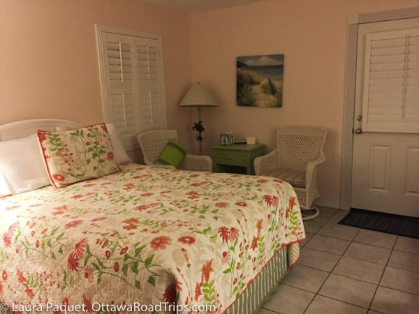 Bed with floral cover and two rattan chairs in English Garden room at Windemere Inn by the Sea in Indialantic, Florida.