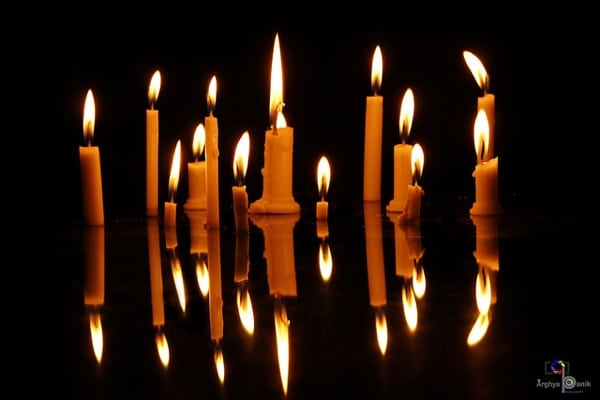A row of candles glowing in the dark.