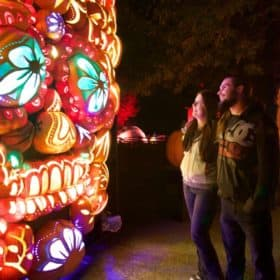 Couple admires multicoloured, illuminated display of artificial pumpkins at Pumpkinferno at Upper Canada Village in Morrisburg, Ontario.