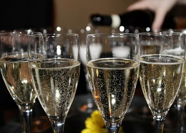 Sparkling wine being poured into multiple glasses.