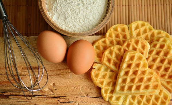 A whisk, two brown eggs, flour and heart-shaped waffles.
