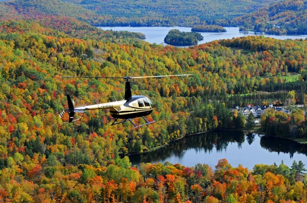 Helicopter flying above hills covered in fall foliage, with lakes, in the Laurentians area of Quebec.