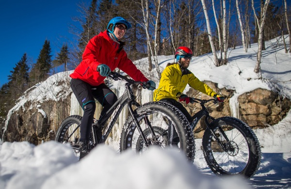 Cyclist in red jacket and cyclist in yellow coat on fat bikes on snowy, hilly trail lined with birch trees in the Mont Tremblant area of Quebec.
