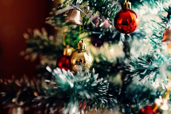 Close-up of red and gold round ornaments on a decorated Christmas tree.