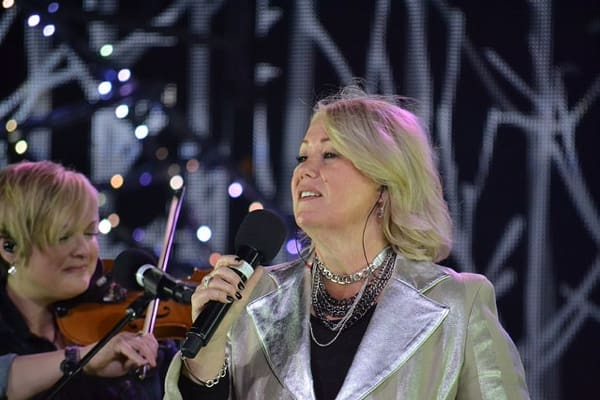 Singer Jann Arden in a silver jacket with a microphone, with a woman playing the fiddle in the background.