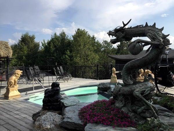 An Asian statue of a dragon or serpent overlooks a pool at Ofuro Spa in Morin Heights, Quebec.