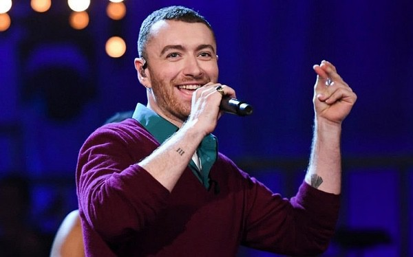 Singer Sam Smith in a purple sweater with a microphone.