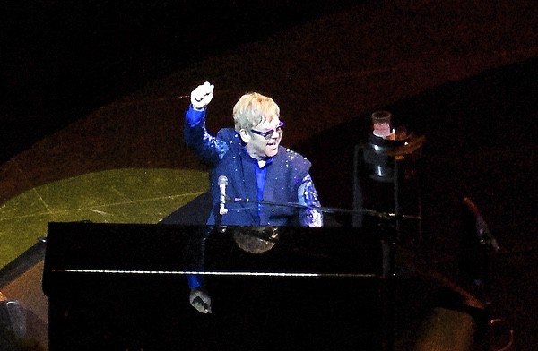 Elton John in a sparkly blue suit at his piano on a dark stage.