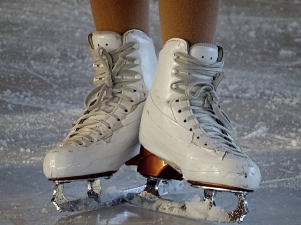 Close-up of a skater's feet with white figure skates (ice skating).
