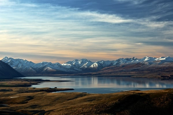 Lake Tekapo in New Zealand surrounded by snow-capped mountains.