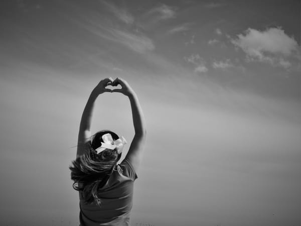 Black and white photo of woman stretching her hands over her head.