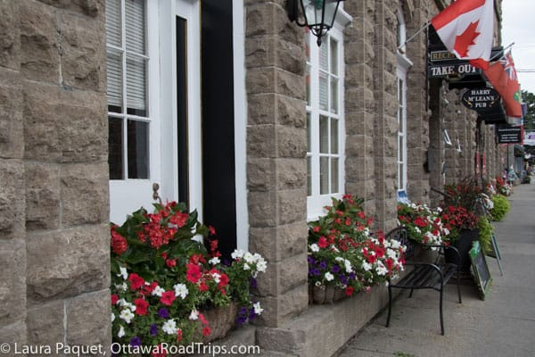 Stone buildings with red and white flowers in window boxes on St. Lawrence Street in Merrickville.