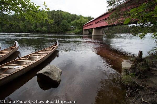 Red covered bridge over the Gatineau River in Wakefield with canoes in foreground.
