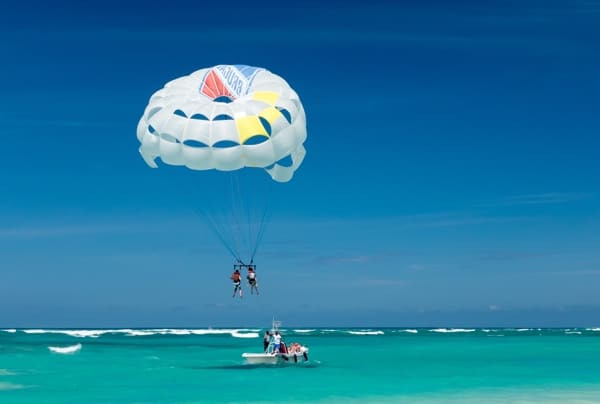 Parasailer in blue sky above blue-green water in Punta Cana, Dominican Republic.