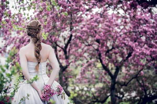 Bride photographed from the back, in a grove of lilacs.