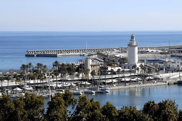 Malaga waterfront with lighthouse and boats.