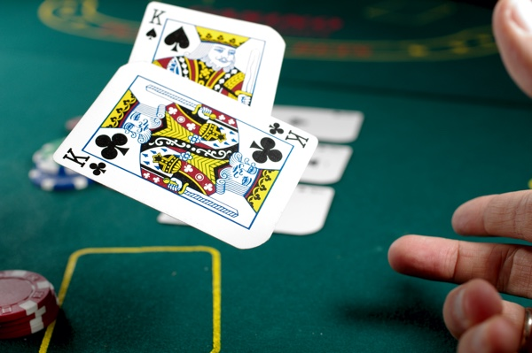 Two playing cards (kings) being tossed on a gaming table in a casino. https://unsplash.com/photos/oT-XbATcoTQ