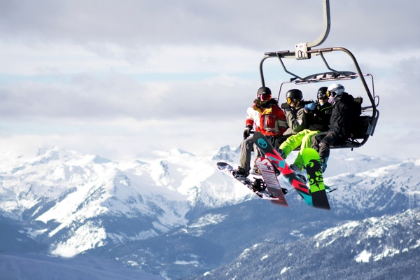 Snowboarders on a lift in Whistler. Photo by Pamela Saunders on Unsplash.