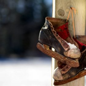 Vintage leather hockey skates hanging on a wooden post.