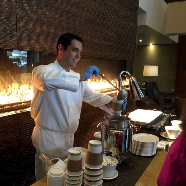 Chef pouring a cup of hot chocolate in front of the fireplace in the lobby of the Westin Ottawa hotel.